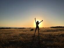 Full Length Of Silhouette Teenage Girl Standing On Field Against Sky During Sunrise