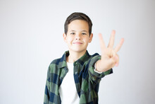 Young Caucasian Little Boy Standing Against White Wall Showing And Pointing Up With Fingers Number Three While Smiling Confident And Happy.