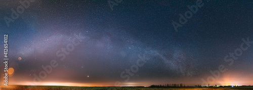 Obraz Night Starry Sky With Glowing Stars Above Countryside Landscape. Milky Way Galaxy And Rural Field Meadow In Early Spring. Panorama, Panoramic View - fototapety do salonu