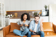 A Multiracial Couple With Joysticks Sits On The Couch At Home And Playing Video Game, An African Woman Is Winner, Scream Happily While Her Boyfriend Feels Upset With A Losing
