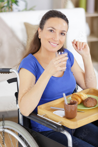 Photo smiling crippled woman having breakfast at home
