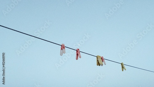Fototapeta premium Low Angle View Of Clips Hanging Against Clear Blue Sky