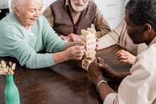Happy Multicultural Pensioners Playing Tower Wood Blocks Game At Home