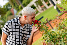 Young Blonde Guy Smelling Rose