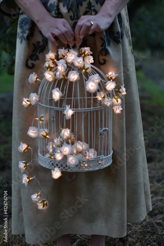 Low Section Of Woman Standing With Illuminated Birdcage Outdoors Fototapet