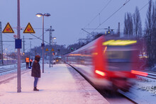 Night Outdoor View On Platform Railway Station, Railway Track Covered By Snow, And Motion Of Regional Train In Düsseldorf, Germany In Winter Season.