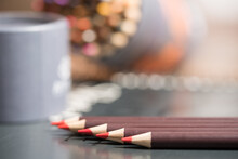 One Red Colored Pencil In Focus.  Diagonal Line Of Other Shades Of Red Colored Pencils And Other Artist Tools Blurred In The Background.