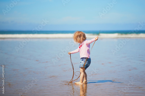 Adorable toddler girl playing with weeds on the sand beach at Atlantic coast of Fotobehang