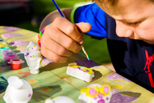 Child Uses His Free Time As A Hobby Painting Plaster Pieces Outdoors.