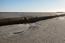 A Thick Rusty Pipeline On A Sandy Beach Near The Ocean At A Beach Replenishment Site