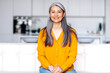 Portrait of a charming asian senior long gray hair lady wearing casual stylish clothes, sitting on couch at living room, looking directly at the camera with friendly smile