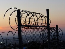 Silhouette Barbed Wire Fence Against Sky During Sunset