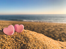 """Two Candy Hearts, One Has The Word """"love"""" On It, On A Beach With Ocean Blurred In The Distance"""