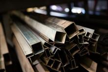 Variety Of Iron Square Tubes, Round Pipes And Shaped Profiles On Rack In Metalworking Shop..
