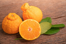 Orange Fruit On Wooden Table , Dekopon Orange Or Sumo Mandarin Tangerine With Leaves In Wooden Background.