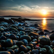 Pebbles At Beach Against Sky During Sunset
