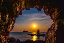 Scenic View Of Sea Seen Through Cave Against Sky During Sunset