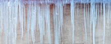 Long Icicles Hang From Roof Gutter In Spring Season