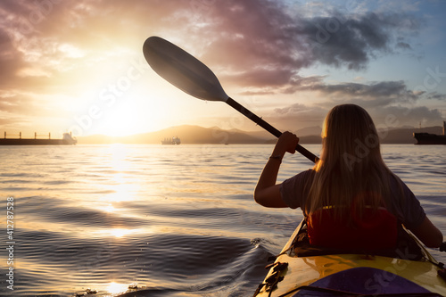 Obraz Woman on a sea kayak is paddling in the ocean during a colorful and vibrant sunset. Taken in Jericho, Vancouver, British Columbia, Canada. Concept: Adventure, Holiday, Vacation, Lifestyle, Freedom - fototapety do salonu