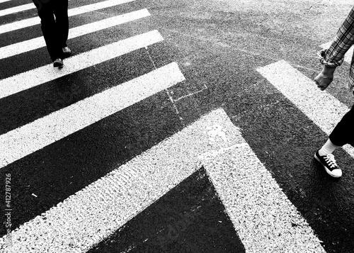 Foto Low Section Of People Walking On Zebra Crossing