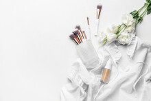 Bottle Of Makeup Foundation, Brushes And Flowers On Light Background