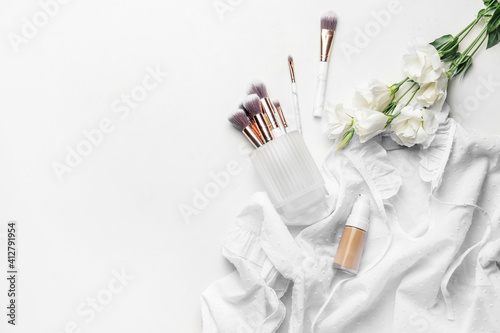 Fototapeta Bottle of makeup foundation, brushes and flowers on light background obraz