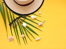 High Angle View Of Seashells By Hat And Eyeglasses Over Palm Leaf On Yellow Background