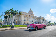 Vintage American Retro Car Carconvertible Rides On An Asphalt Road In Front Of The Capitol In Old Town Havana. Tourist Taxi Cabriolet.