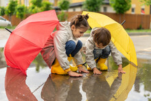Happy Children Play In A Puddle After The Rain. Brother And Sister Hid Under Umbrellas And Touched Water. Kids Having Fun On The Street