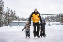 Young Caucasian Bearded Man Teach Boys How To Skate, Holding Hands. Father's Day Concept. Cute Caucasian Boys Learning To Skate. Image With Selective Focus