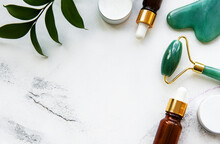 Face Massage Jade Roller With Cosmetic Product On White Marble Background