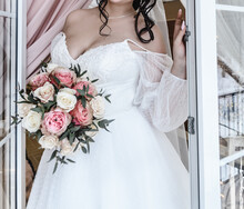 Young Beautiful Bride In A White Delicate Elegant Airy Wedding Dress With A Bouquet Of Flowers Rose