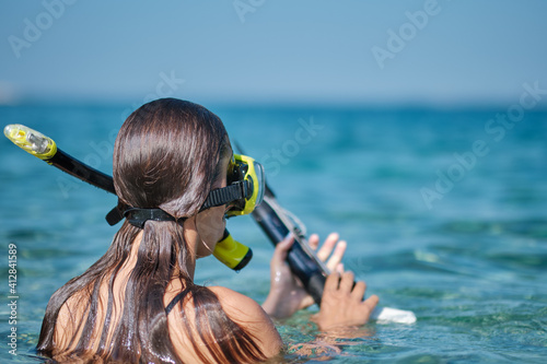 A woman in a bikini hunts with a crossbow Fototapet