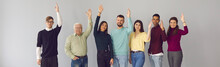 Group Portrait Of Diverse People Standing With Arms Raised And Voting Against Gray Wall Background. International Business People In Casual Clothes Make Decisions By Voting. Concept Of Solidarity.