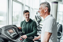 Close Up In Focus Of An Older Man's Face, He Is Looking Ahead And Performing A Cardio Exercise, In The Background His Rehabilitation Coach