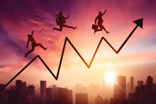 Three Business People Jumping With Upward Arrow