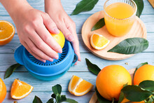 Woman Squeezing Fresh Orange Juice On Blue Table, Top View