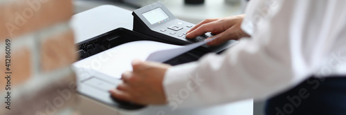 Obraz Woman in office prints documents on printer. Scanning documents at workplace concept - fototapety do salonu