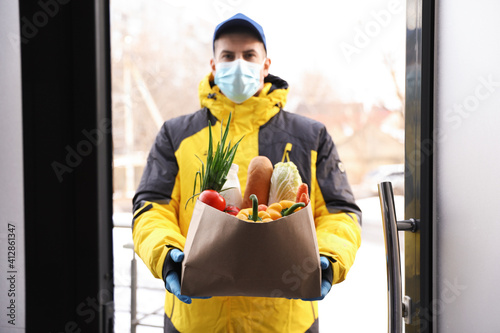 Courier in medical mask holding paper bag with groceries at doorway. Delivery service during quarantine due to Covid-19 outbreak © New Africa
