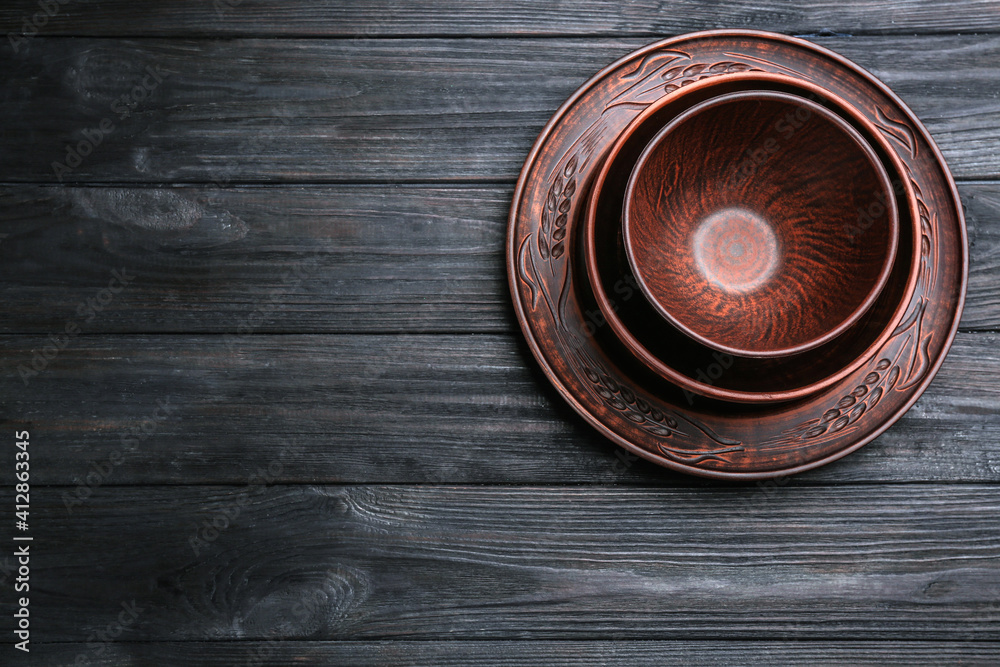 Fototapeta Set of clay dishes on black wooden table, top view. Space for text