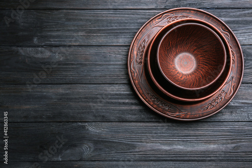 Fototapeta Set of clay dishes on black wooden table, top view. Space for text obraz