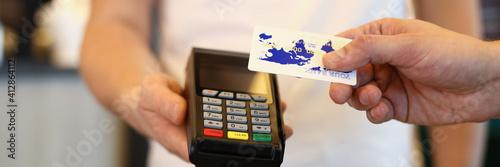Fotografia Man applies card to terminal and makes payment