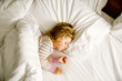 canvas print picture - Cute little toddler girl sleeping in big bed of parents. Adorable baby child dreaming in hotel bed on family vacations or at home.
