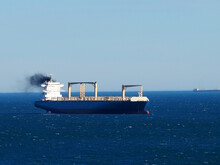 Black Smoke From The Chimney Of A Large Transport Ship Sailing On The Sea