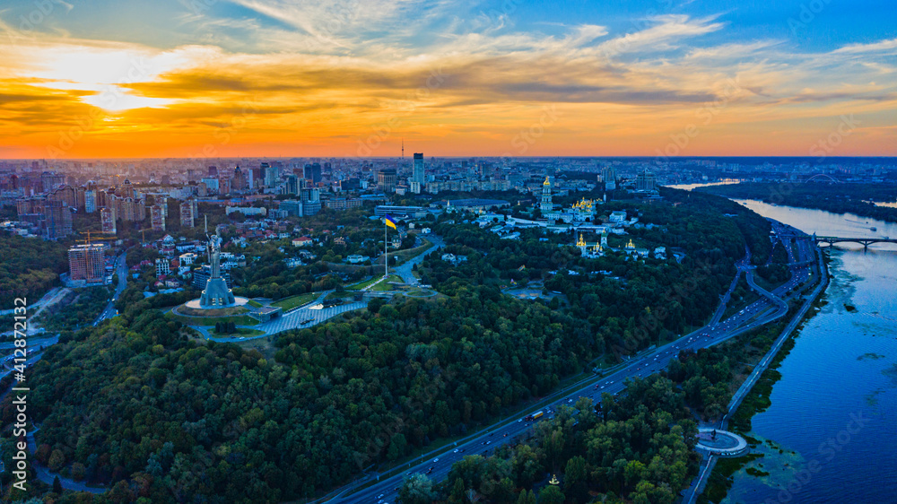 Fototapeta Aerial view to the  Beautiful landscape city Kiev with a Dnepr river while sunset. Top view to the city Kiev in the summer. Beautiful city Kiev while sunset.