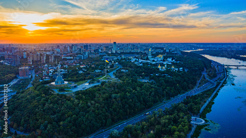 Fototapeta Aerial view to the  Beautiful landscape city Kiev with a Dnepr river while sunset. Top view to the city Kiev in the summer. Beautiful city Kiev while sunset. obraz