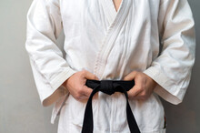 A Man In Kimono Is Holdong His Black Belt