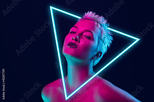 Fototapeta Future. Portrait of female fashion model in neon light with neoned blue glowing triangle on dark studio background. Beautiful woman with trendy make-up and well-kept skin. Vivid style, beauty concept. obraz