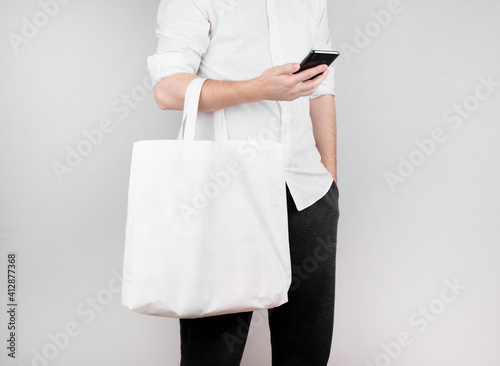 Obraz a man stands on a white background, reads the news on the phone and holds an ecological bag made of flax on his elbow. Ecology Concept - fototapety do salonu