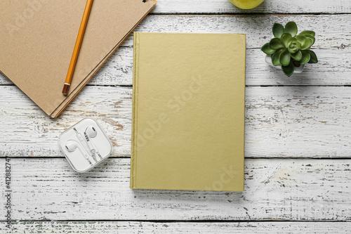 Fototapeta Blank book, earphones and plant on wooden background obraz